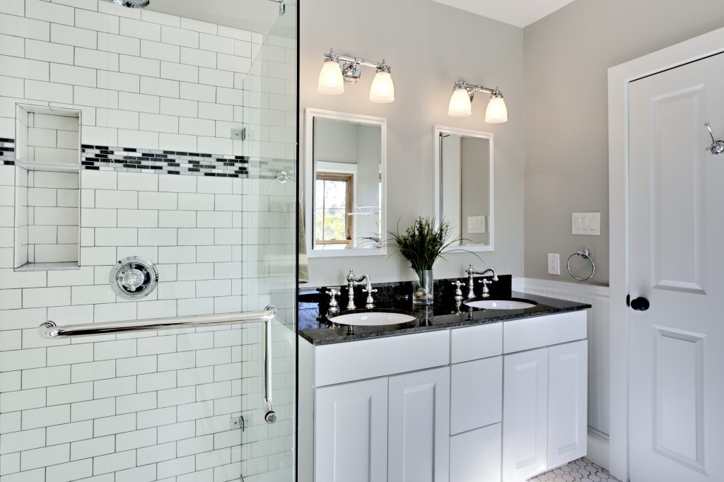 Bright white remodel bathroom. Glass shower and granite counters.